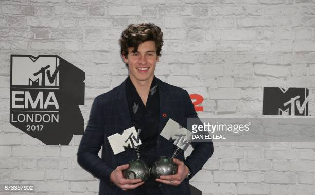 TOPSHOT Canadian singersongwriter Shawn Mendes poses with two of his three awards for best song for 'There's Nothing Holdin' Me Back' best artist and...