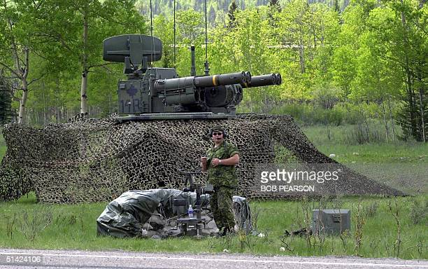 Canadian soldier keeps watch near an Air Defense AntiTank System rocket launcher 22 June 2002 near Kananaskis Alberta Canada as preparations continue...
