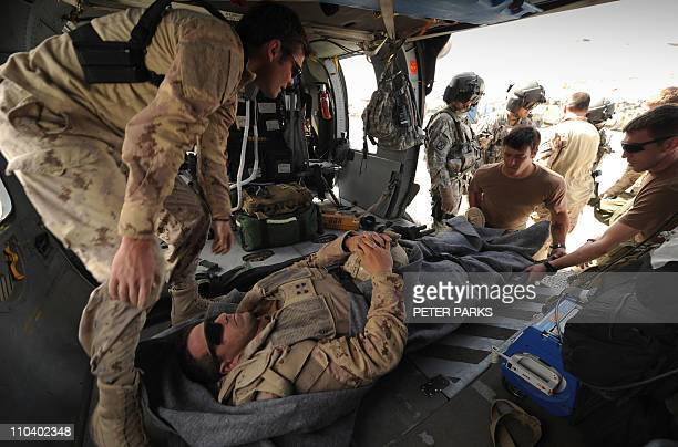 A Canadian soldier with a suspected appendicitis is treated by a medic from Company C 1st Battalion 52nd Aviation Regiment MEDEVAC unit on a...