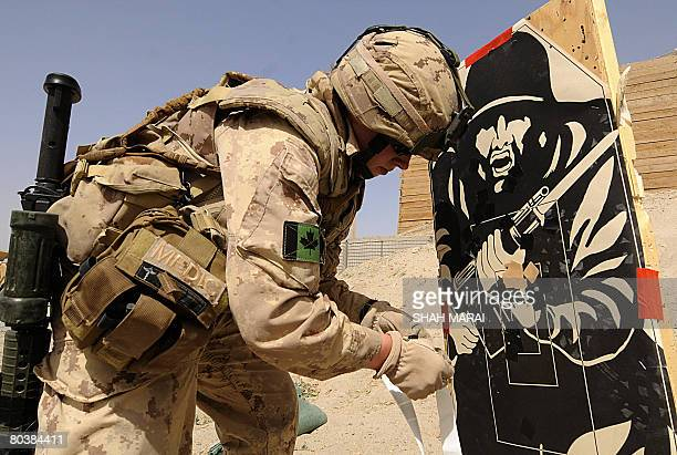 A Canadian soldier with the NATOled International Security Assistance Force inpects a target after an exercise at the base of Provincial...