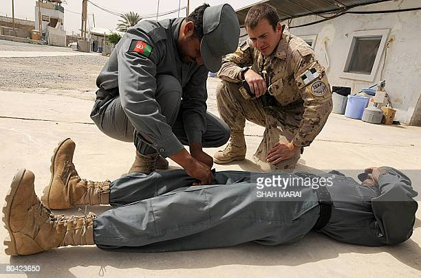 A Canadian soldier with the NATOled International Security Assistance Force watches Afghan policemen practice a first aid technique during a training...