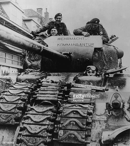 Canadian soldiers adding 'Caput' to the Wehrmacht Headquarters sign on a tank after liberating the Dutch town of Almelo 18th April 1945