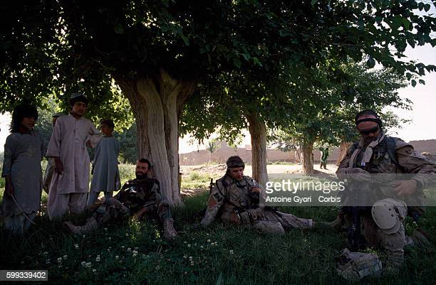 Canadian soldiers from the Operational Mentoring and Liaison Team and soldiers of the Afghan National Army take a rest under a tree while patroling...