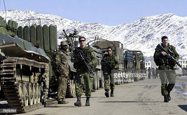 Canadian soldiers of the NATOled International Security Assistance Force patrol by amoured vehicles lined up in Kabul 10 Februay 2004 The vehicles...