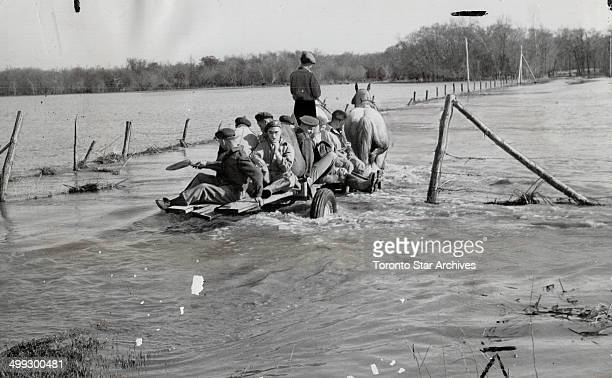 Canadian soldiers ride on a farmer's wagon through flood waters of the Assiniboine river as they travel assists volunteers in plugging dykes in the...