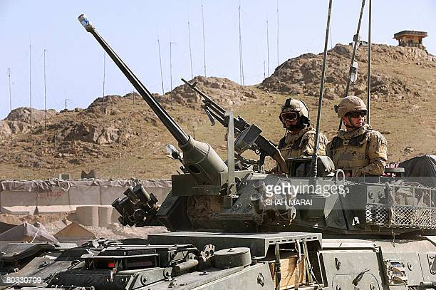 Canadian soldiers with the NATOled International Security Assistance Force sit on top of their armoured vehicle as they go on a joint foot patrol...