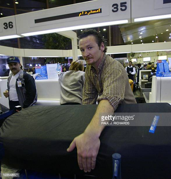 Canadian teacher at the American International School in Kuwait Don Alguire of Ottawa picks up his luggage and checks in for his flight home as all...
