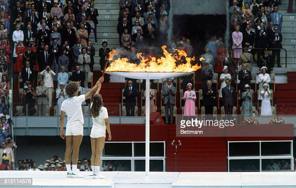 Canadian teenagers Sandra Anderson and Stephen Prefontaine jointly light the Olympic urn in the stadium by passing the flame from their torch 7/17