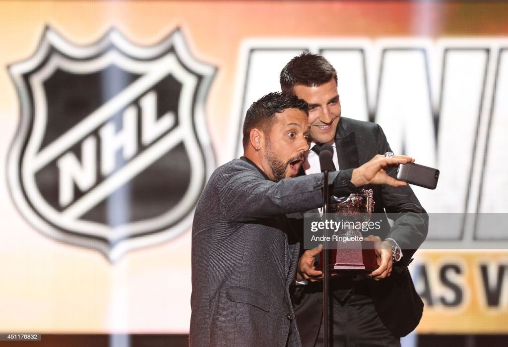 Canadian television and radio personality George Stroumboulopoulos takes a selfie photo with Patrice Bergeron of the Boston Bruins after Bergeron won the Frank J. Selke Trophy during the 2014 NHL Awards at the Encore Theater at Wynn Las Vegas on June 24, 2014 in Las Vegas, Nevada.
