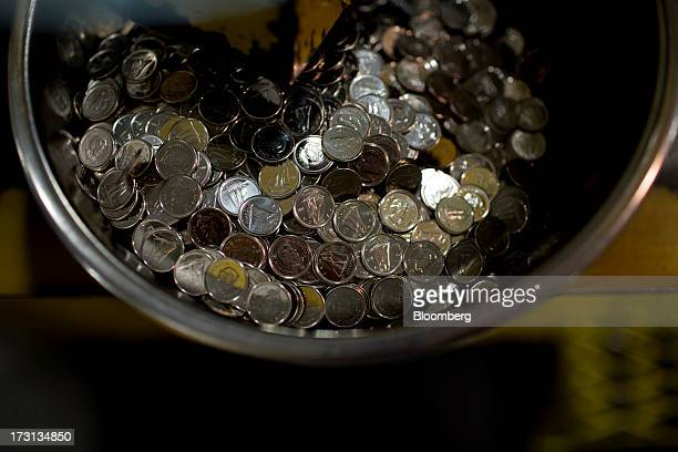 Canadian ten cent coins sit in a container at the Royal Canadian Mint in Winnipeg Ontario Canada on Friday July 5 2013 The Canadian dollar rose from...