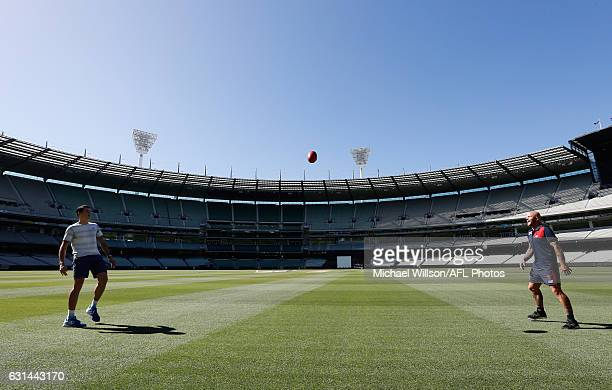 Canadian tennis player Milos Raonic and Melbourne AFL captain Nathan Jones kick the football during a Melbourne Demons AFL media opportunity at...