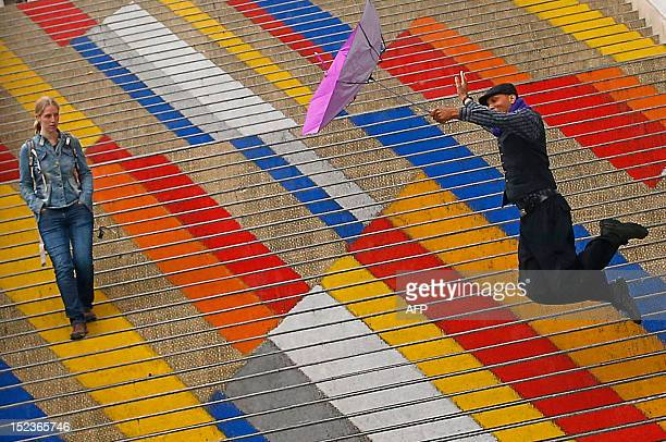 A Canadian tourist holds an umbrella as he jumps on the colored steps of the Albertina museum during a rainy day in Vienna on September 19 2012 AFP...