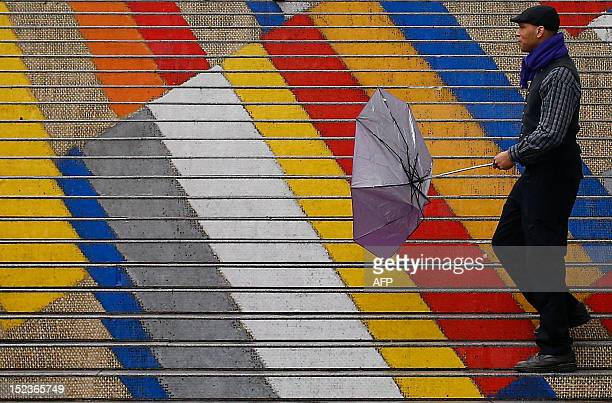 A Canadian tourist holds an umbrella as he walks on the colored steps of the Albertina museum during a rainy day in Vienna on September 19 2012 AFP...
