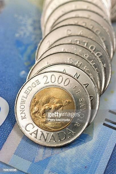 Canadian two dollar coins on a bank note