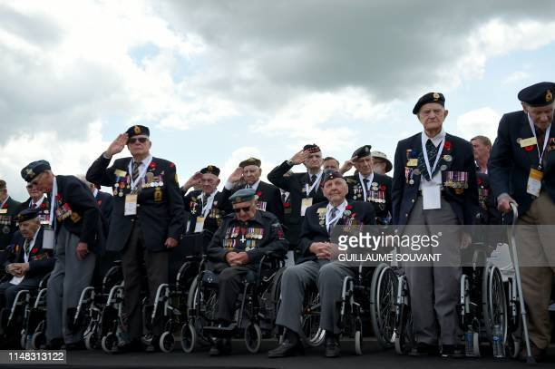 Canadian veterans stand for the National Anthem during the international ceremony on Juno Beach in Courseulles-sur-Mer, Normandy, northwestern...