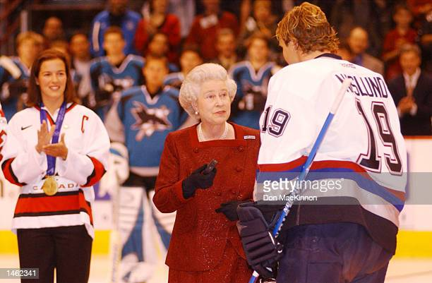Canadian Womens Olympic winter games gold medal hockey team captain Cassie Campbell watches as Vancouver Canucks captain Markus Naslund hands Queen...