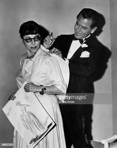 Canadianborn actor Glenn Ford autographs one of the sketches American costume designer Edith Head created for the film 'Pocketful Of Miracles' on...