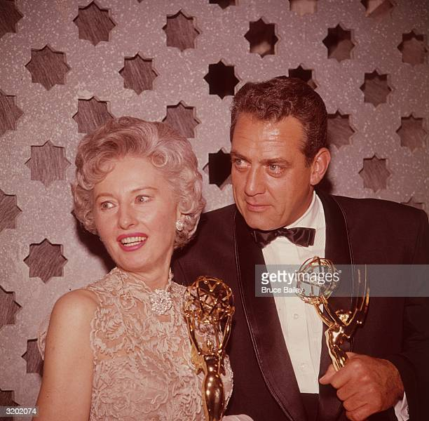 Canadianborn actor Raymond Burr and American actor Barbara Stanwyck smile while holding Emmy Awards backstage Burr won Outstanding Single Performance...