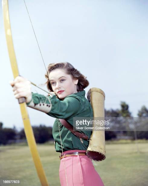 Canadian-born actress Alexis Smith aiming a bow and arrow, circa 1945.