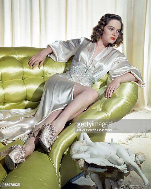 Canadianborn actress Alexis Smith reclining on a green leather sofa and wearing a satin evening gown and highheeled shoes circa 1945
