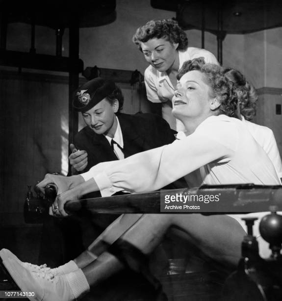 Canadianborn actress Alexis Smith uses a rowing machine while a police officer times her with a stopwatch USA circa 1951
