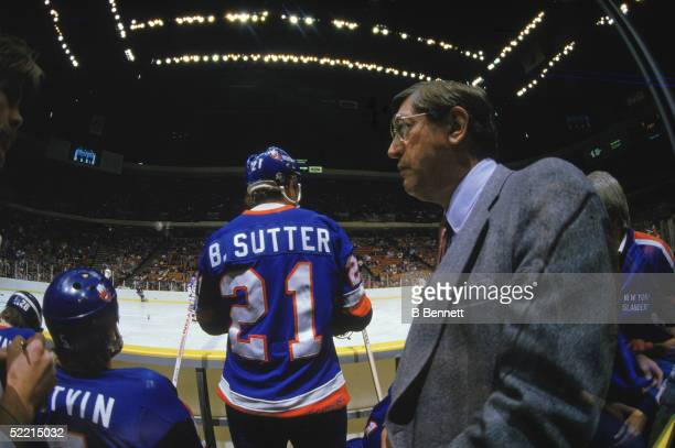 Canadianborn Al Arbour coach of the New York Islanders and team captain Brent Sutter watch warmups from the bench before a game at the Brendan Byrne...