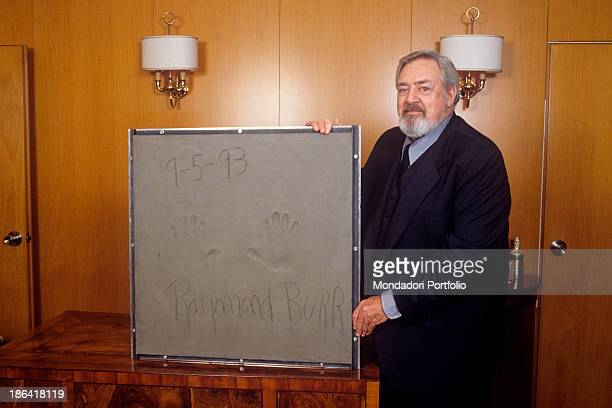 Canadianborn American actor Raymond Burr showing a tile with his handprints and his autograph The relic will be placed in corso Europa at the...