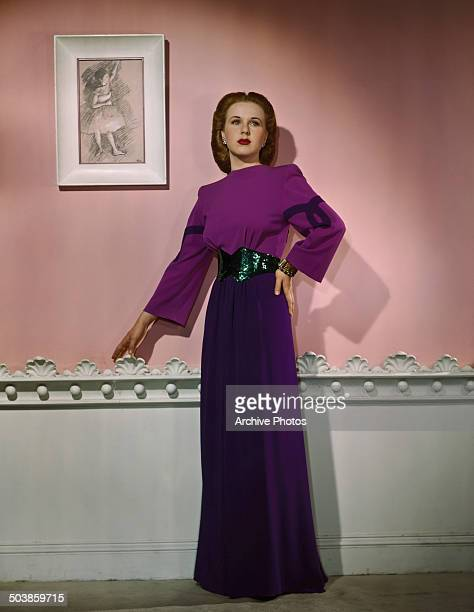Canadianborn American actress and singer Deanna Durbin wearing a purple evening gown 1946 On the wall behind her is a Degas sketch of a ballerina