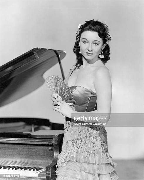 Canadianborn American actress Yvonne De Carlo standing next to a piano circa 1950