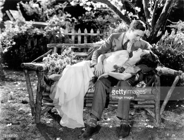 Canadianborn American film actor and novelist David Manners born Rauff de Ryther Daun Acklom holds American actress Ann Dvorak in his arms on his lap...