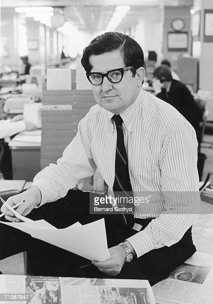 Canadianborn American managing editor of the New York Times newspaper AM Rosenthal sits on a desk covered with newspapers and holds documents in the...