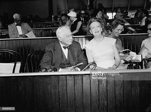 Canadianborn beautician and cosmetics entrepreneur Elizabeth Arden and American financier and statesman Bernard Baruch sit in a box at the Saratoga...