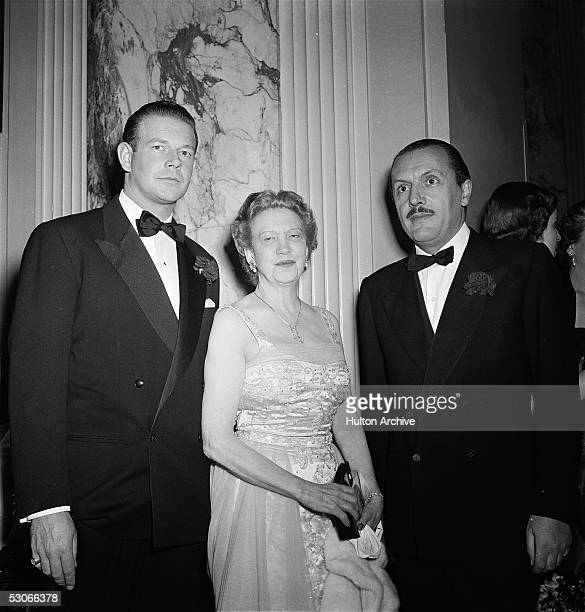 Canadianborn beautician and cosmetics entrepreneur Elizabeth Arden wearing an evening gown stands with fashion designer Count Fernando Sarmi and one...