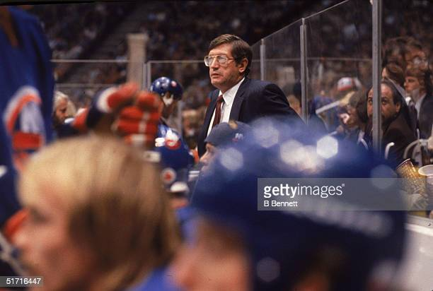 Canadianborn hockey coach and former hockey player Al Arbour head coach of the New York Islanders watches from the bench area during a game against...