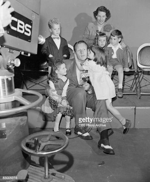 Canadianborn television host Art Linkletter poses with a group of children one of whom kisses him on the cheek in front of a television camera on the...