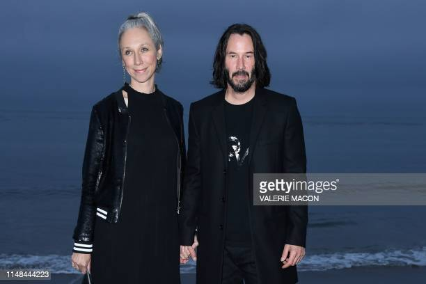 CanadianUS actor Keanu Reeves and US artist Alexandra Grant arrive for the Saint Laurent Men's SpringSummer 2020 runway show in Malibu California on...