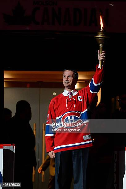 Canadiens alumni Guy Carbonneau holds the flame up during the pre game ceremony prior to the NHL match against the New York Rangers at the Bell...