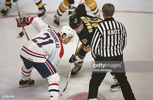 Canadiens center Guy Carbonneau and Bruins counterpart Thomas Gradin wait for linesman Swede Knox to drop the puck at the Montreal Forum during the...