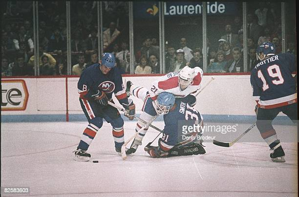 Canadiens forward Guy Carbonneau falls on Islander goaltender Billy Smith in a game at the Montreal Forum during the 198687 season
