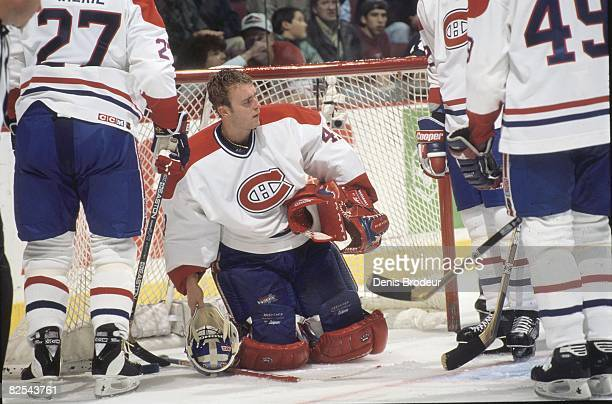 Canadiens goaltender Jocelyn Thibault kneels in his crease while play is stopped in a game at the Molson Centre during the 199697 season Teammates...