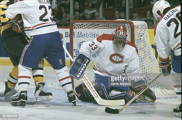 Canadiens goaltender Patrick Roy watches as teammate Yves Racine takes charge of the puck while forward Brian Bellows keeps Bruins opponent at a safe...