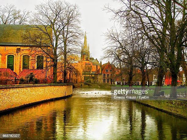 canal amidst bare trees and buildings against sky - krausz stock-fotos und bilder