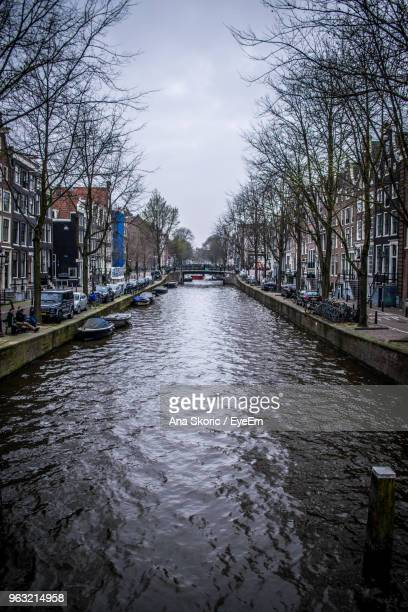 Canal Amidst Bare Trees And Buildings Against Sky