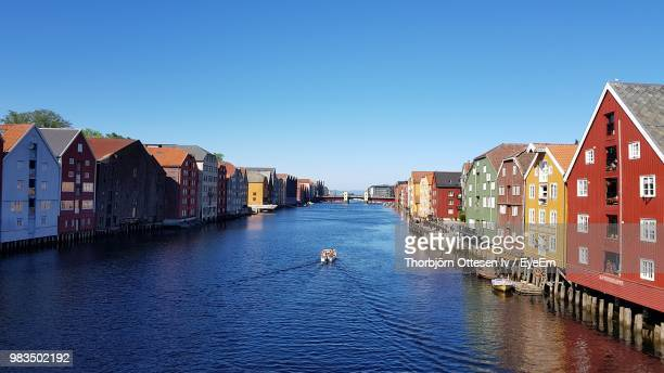 canal amidst buildings against clear blue sky - トロンハイム ストックフォトと画像