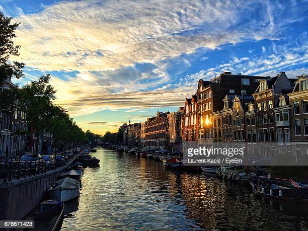 Canal Amidst Buildings Against Cloudy Sky During Sunset