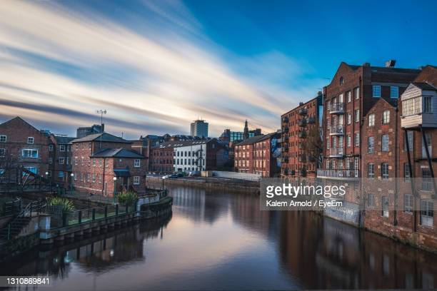 canal amidst buildings against sky at dusk - leeds stock pictures, royalty-free photos & images
