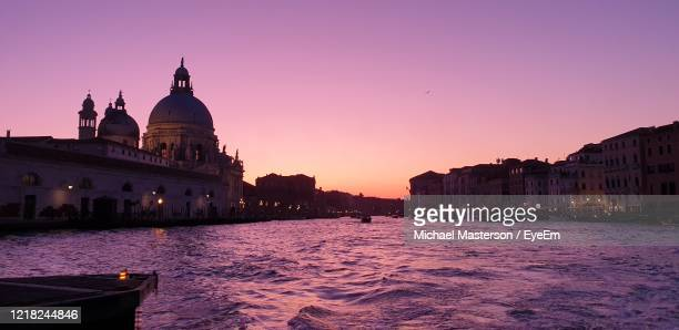 canal amidst buildings against sky at sunset - venice italy stock pictures, royalty-free photos & images