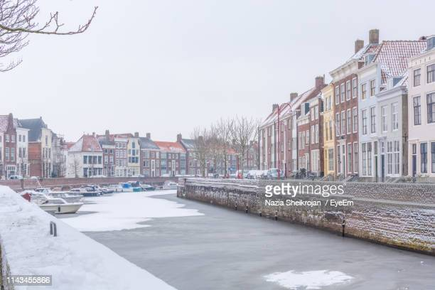 canal amidst buildings against sky during winter - middelburg netherlands stock pictures, royalty-free photos & images
