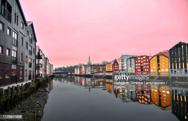 canal amidst buildings against sky in city - trondheim stock pictures, royalty-free photos & images