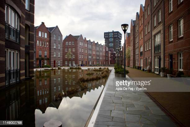 canal amidst buildings against sky in city - the hague stock pictures, royalty-free photos & images
